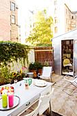Gedeckter Tisch im Hinterhofgarten mit Mini-Büro im Gartenhaus