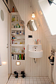 Small bathroom under the slope with skylight and built-in shelving