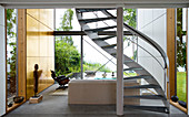 A curved staircase in the living room of a modern architectural house