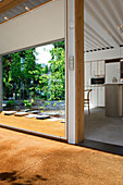 Glazed wall in the hallway with coconut carpet to the open kitchen
