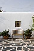 Gartenbank unterm Fenster mit Gitter am mediterranen Haus
