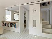 Offener Wohnraum in Weiß mit gewendelter Treppe und offener Küche