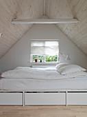 Bett mit Bettkästen im kleinen Schlafzimmer unter der Schräge