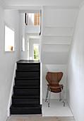 Stapel Designerstühle unter der Treppe mit schwarzen Stufen