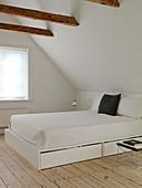 Bett mit Bettkästen im schlichten Schlafzimmer unter der Schräge