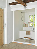 View from the hallway with wooden beams into the small bathroom with bathtub