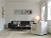 White armchair in front of a black sofa in a minimalist living room