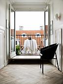 Black designer chair in front of an open balcony door