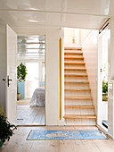 A hallway with stairs and a view into the bedroom on a houseboat