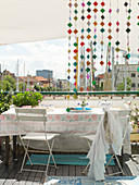 A colourful bead curtain at a garden table with a view of the city
