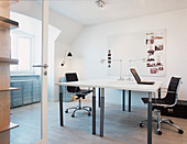 Two swivel chairs at opposite desks in the study