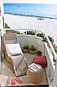 Wicker chaise lounge on a seaside sunny terrace