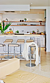 Bar stool at the high table in front of the open kitchen