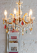 A colourful chandelier in front of a white wall with magazine rack
