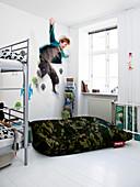 Junge springt vom Hochbett auf einen Sitzsack mit Flecktarn