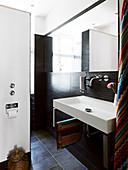Eckiges Waschbecken im kleinen Bad mit dunklen Fliesen