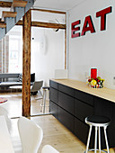 Red lettering above the black kitchenette in the open living room