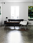 Rocking chair in front of coffee table and sofa on a concrete floor
