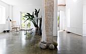 Steine um einen Backsteinpilaster im offenen Wohnraum mit Betonboden