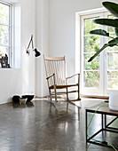 Rocking chair in front of garden door in minimalist living room with concrete floor