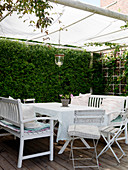 A sheltered seating area on a covered terrace with white furniture