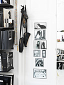 Ballet shoes hanging next to a bookcase and black-and-white photos