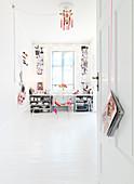 Blick durch offene Tür in die Küche mit weißem Boden und offenen Regalen