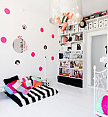 reading nook in front of the wall with pink dots and the shelf in the nursery