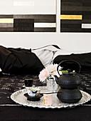 Asian iron teapot and dahlias on silver tray