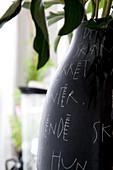 Schwarze Vase mit weißer Handschrift verziert