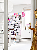 A golden Buddha in front of an open door to an office with a collage on the wall