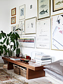 Wooden bench with books and small bowls and indoor plant in the living room with a collection of pictures and illustrations