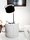Table lamp and alarm clock on a white bedside table