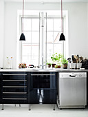 Black high-gloss kitchen with stainless steel worktop in an old building with white plank floor