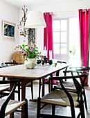 Designerstühle am Esstisch vorm Fenster mit pinken Vorhängen