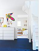 Flur mit blauem Boden, Treppe und Blick ins Wohnzimmer