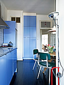 Retrostühle und Designerleuchte in der Wohnküche mit blauen Fronten