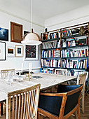 Different chairs at the dining table in front of the bookshelf and a salon style picture wall