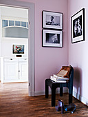 Black chair in front of a pink wall with black and white photos in the hallway