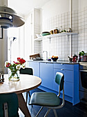 Round table and retro chairs in living room kitchen with blue fronts