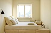 Matratze auf einem Podest mit Schubladen im schmalen Schlafzimmer