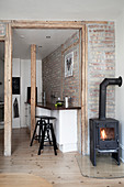 woodstove in the corner of the room, view of the kitchen with breakfast bar in front of a brick wall