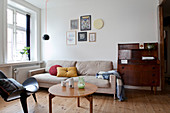 An antique bureau, a sand-coloured sofa, a coffee table and a designer chair in a living room