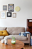 Antique secretary, sand-colored couch, coffee table and designer chair in the living room
