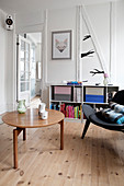 A coffee table, a black designer chair and a half-high shelf in a living room