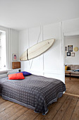 Double bed with bedspread in the bedroom with rustic floorboards, surfboard on white wall