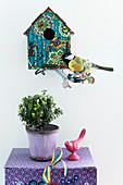 Vogelhäuschen und Dekovogel an der Wand, darunter Topfpflanze