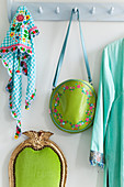 Coat rack with bag and colourful cloth, below green chair