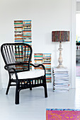 Black rattan chair in front of a pile of books and magazines with a table lamp