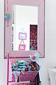 Rosa Korb mit Tüchern vor Wandspiegel rosa gestrichenem Holzrahmen